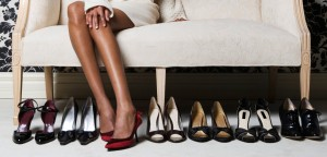 Woman sitting on sofa, trying on shoes